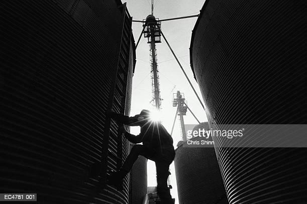 Farmer climbing storage silos, low angle view (B&W)