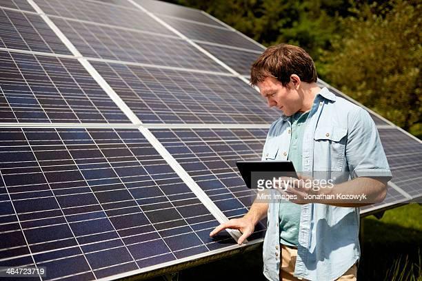 A farmer closely inspecting the surface of a solar panel on the farm.