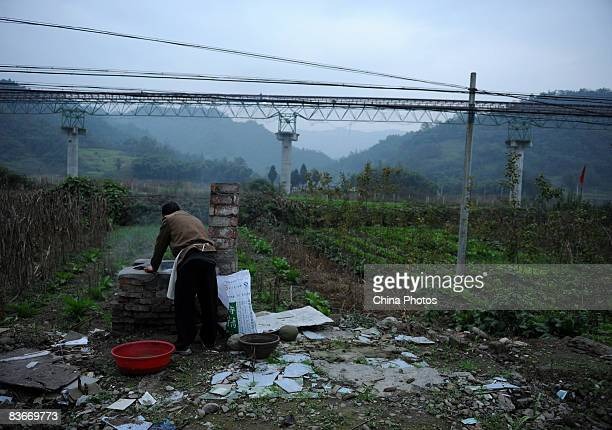 A farmer cooks supper outdoors on a field where his house was destroyed in the Sichuan Earthquake on November 12 2008 in Pengzhou of Sichuan Province...