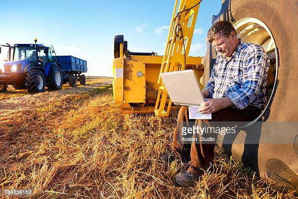Farmer counts profits on a computer
