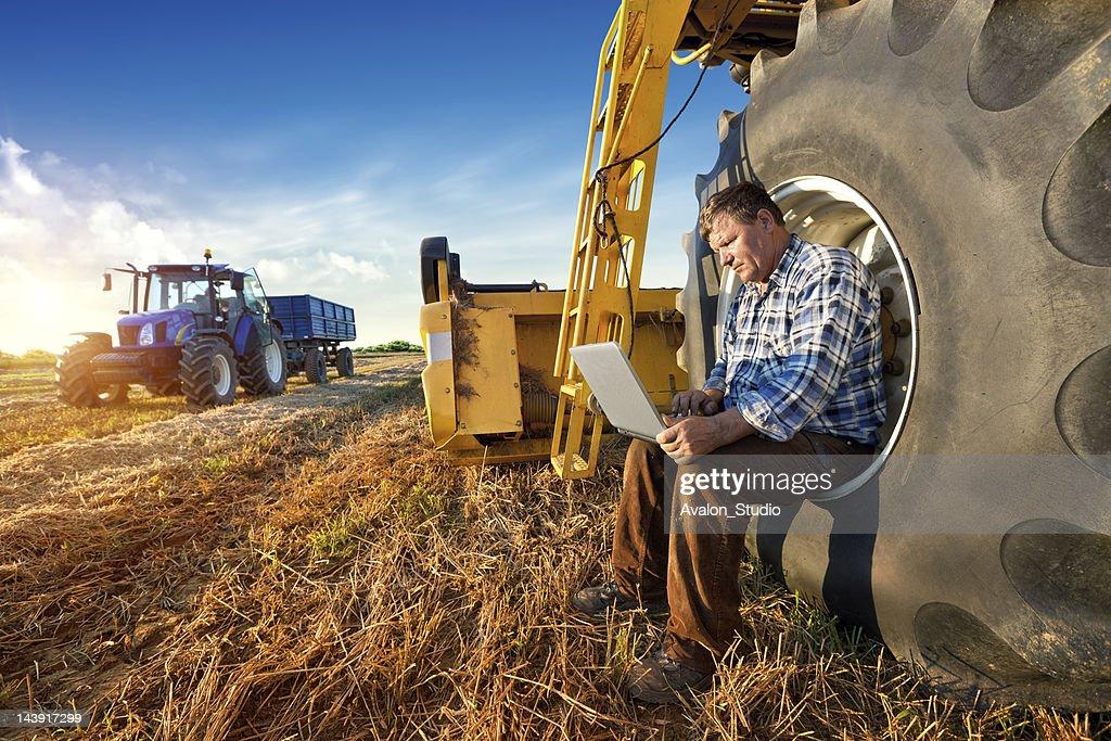 Agricultor y su computadora portátil : Foto de stock