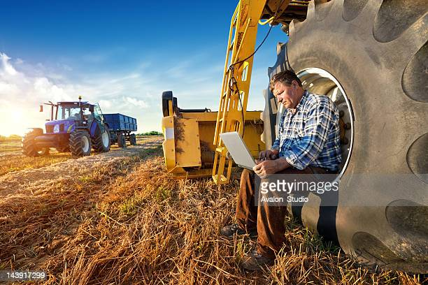 farmer counts yields on a computer - tractor stock pictures, royalty-free photos & images