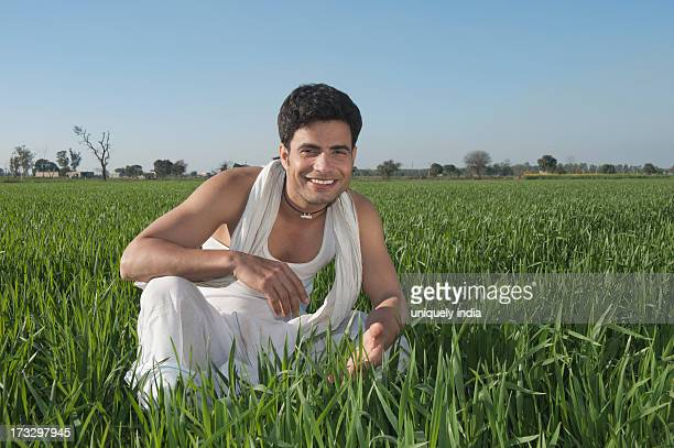 Farmer crouching in the field and smiling, Sonipat, Haryana, India