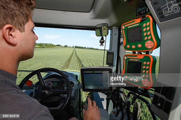 A farmer demonstrates use of a John Deere Co Greenstar 2630 terminal left AmazonenWerke H Dreyer GmbH GPS Switch top right and Amatron terminals...