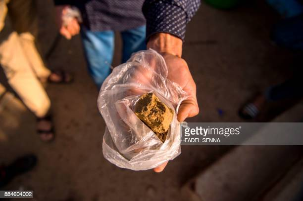 A farmer displays a piece of cannabis resin near the town of Ketama in Morocco's northern Rif region on September 13 2017 Moroccan law bans the sale...