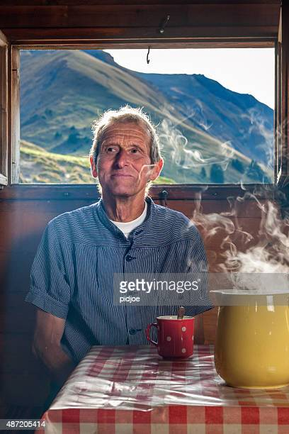farmer drinking coffee in farmhouse, Switzerland