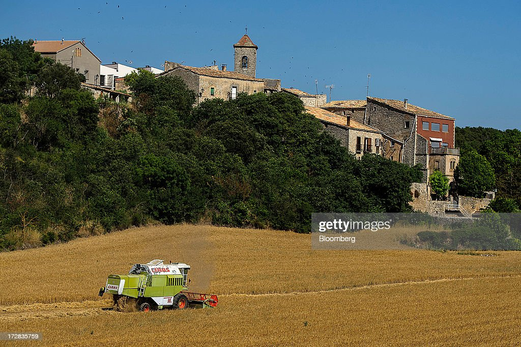 A farmer drives a Claas Dominator 98 combine harvester past village buildings during a barley harvest in Cervera, Spain, on Thursday, July 4, 2013. Spain consumes about 28 million to 30 million tons of grain a year, of which two-thirds is produced domestically, according to young farmers organization Asaja. Photographer: David Ramos/Bloomberg via Getty Images