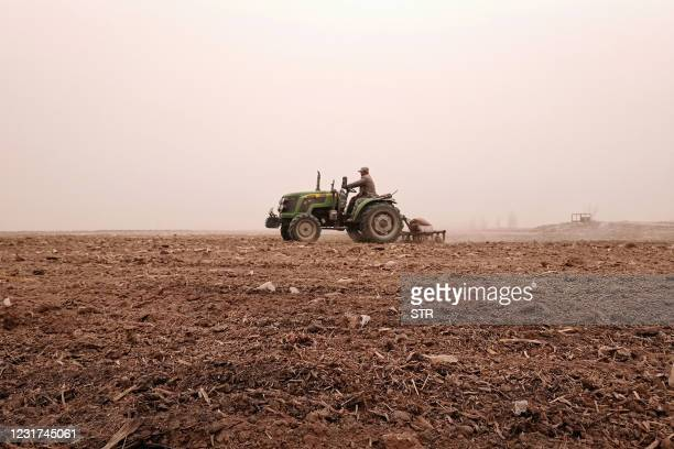 Farmer drives a tractor to plough a field on a polluted day in Zhangye, in northwestern China's Gansu province on March 16, 2021. - China OUT / China...