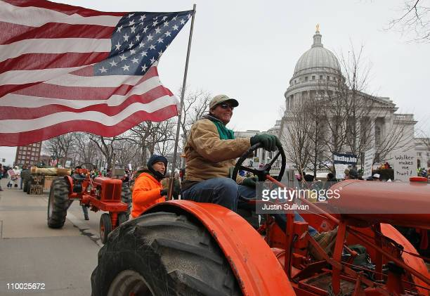 A farmer drives his tractor in a tractorcade during a demonstration outside of the Wisconsin State Capitol on March 12 2011 in Madison Wisconsin Tens...