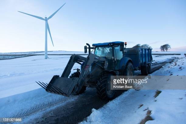 Farmer drives through a wind farm with his load in the Scottish Borders, 25th of January 2021, Scotland, United Kingdom. It has been snowing in...