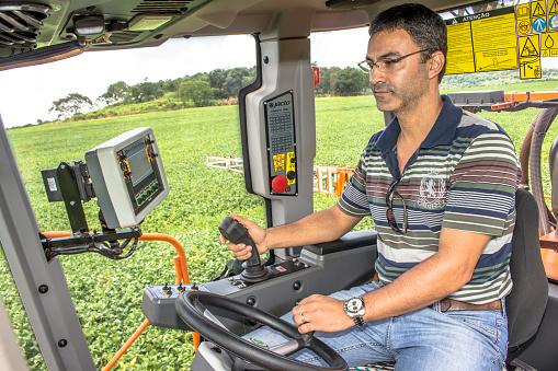 Farmer drives tractor on green soy field in Brazil - gettyimageskorea