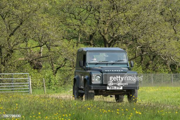 Farmer driving a Land Rover Defender over a field, Lancashire, UK.