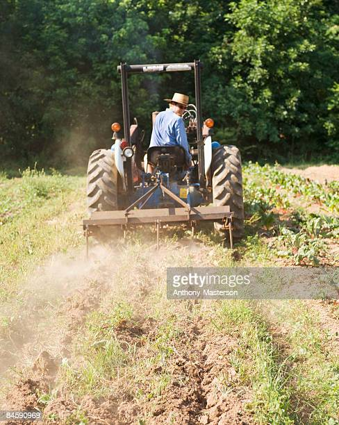 farmer driving a tractor in a field - anthony-masterson stock pictures, royalty-free photos & images
