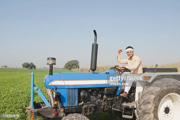 Farmer driving a tractor in the field, Sonipat, Haryana, India