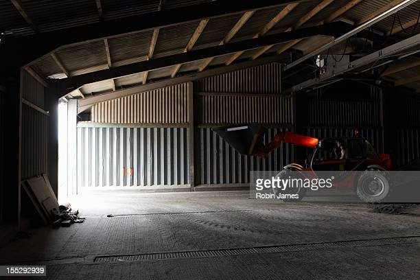 Farmer driving digger in shed