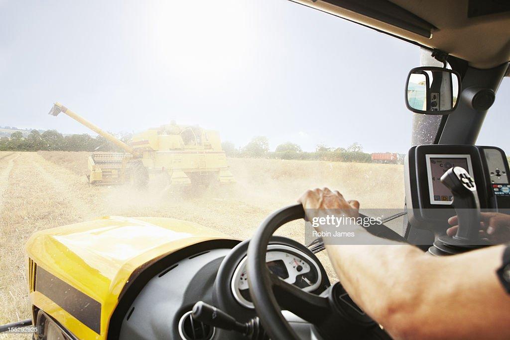 Farmer driving thresher in crop field : Stock Photo