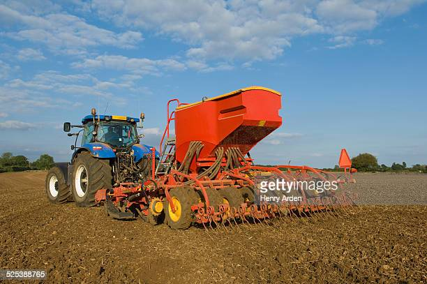 farmer driving tractor and drilling seed corn in field - seed stock pictures, royalty-free photos & images
