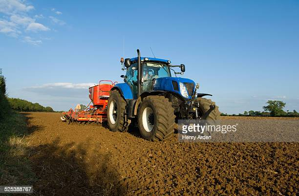 farmer driving tractor and drilling seed corn in ploughed field - トラクター ストックフォトと画像