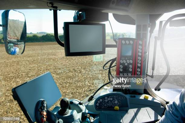 Farmer driving tractor using global positioning system