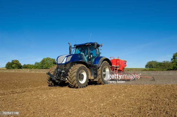 Farmer driving tractor with seed drill in ploughed field in spring