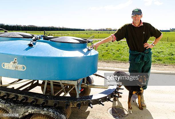 Farmer Erwin Lutz and his dog Bounce stand next to a mobile calf feeder on Lutz Farm which supplies milk to Fonterra Cooperative Group Ltd in Otaki...