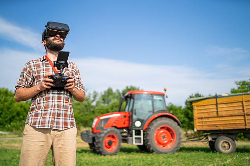 Farmer flying a drone over a field, and using VR headset - gettyimageskorea