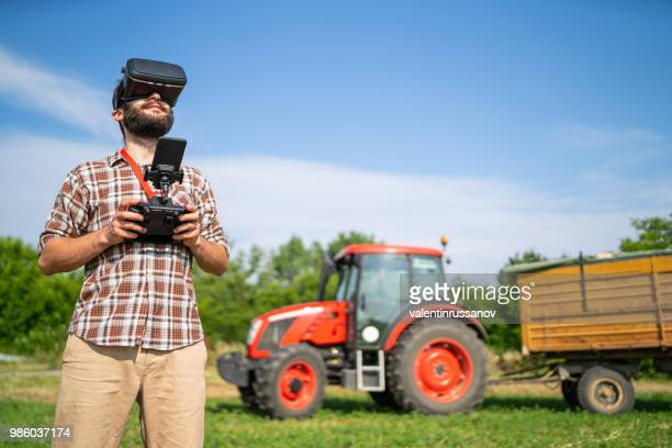 farmer flying a drone over a field, and using vr headset - drone foto e immagini stock