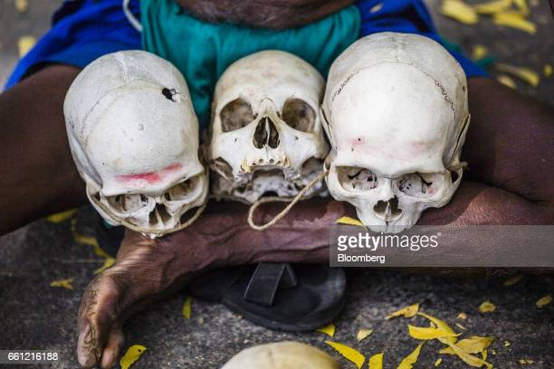 A farmer from the southern state of Tamil Nadu sits on the ground with the skulls of farmers who have committed suicide in their region during a...