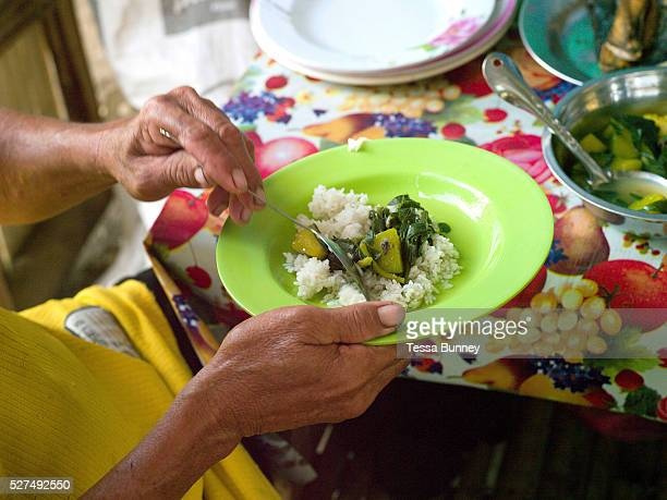 Farmer Geronio Ayson eating homegrown vegetables and rice for lunch Pamantingan Esperanza Mindanao Island The Philippines Geronio and his wife...