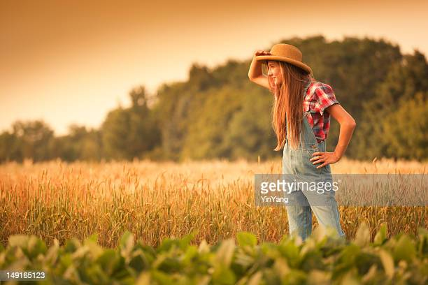 farmer girl looking into distance in the field - guess jeans stock photos and pictures