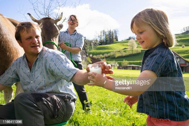 Farmer giving his daughter a glass of fresh milk from a cow on pasture