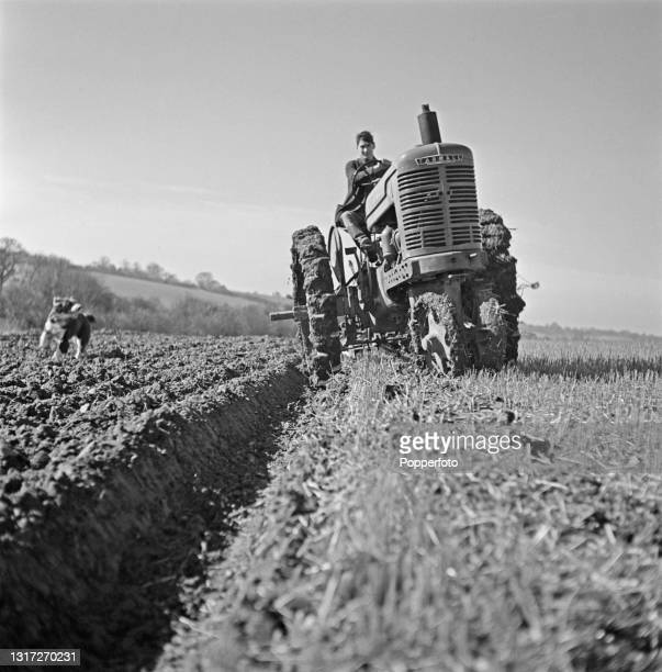 Farmer Harry Smith drives a Farmall H tractor to plough a field on his father Ernest Smith's arable farm near Ware in Hertfordshire, England during...