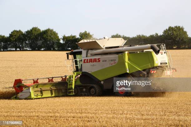 Farmer harvesting a wheat using a Class Lexion 600 Terra Track combine harvester is seen in Brackrade Germany on 25 July 2019