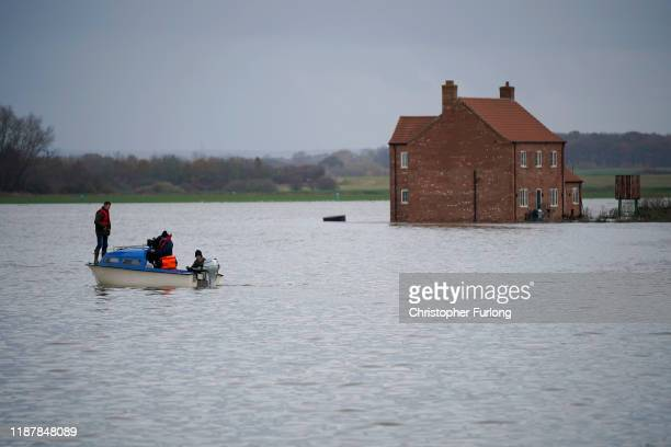 Farmer Henry Ward aged 28 stands on a boat the only access to his flood marooned farm at Bardney near Lincoln after the Barlings Eau broke its banks...