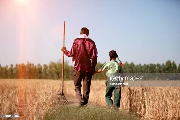 Agriculteur & sa fille marchant dans le champ de blé