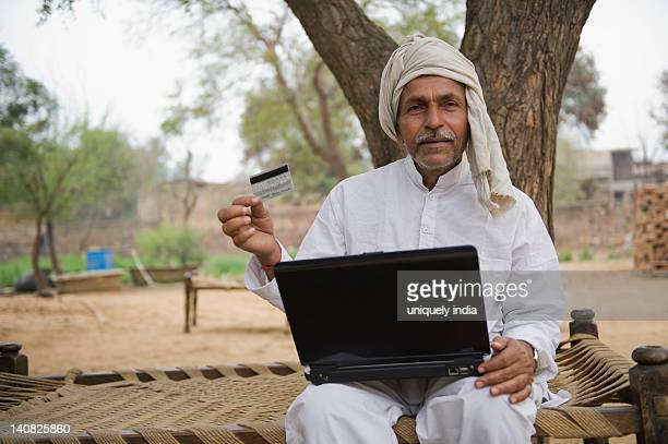 Farmer holding a credit card and using a laptop, Hasanpur, Haryana, India