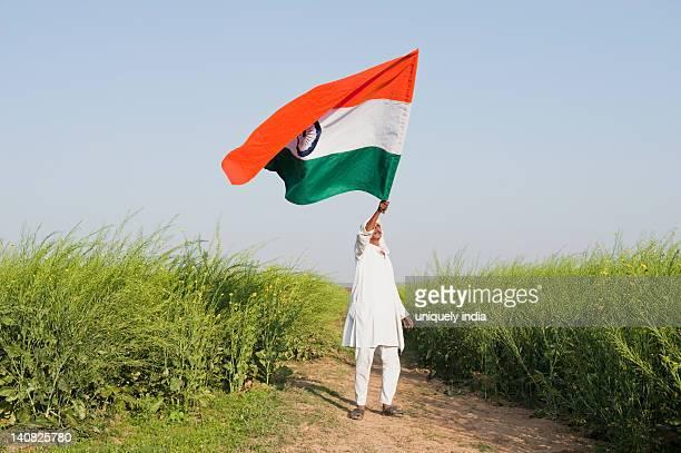 Farmer holding an Indian flag near an oilseed rape field