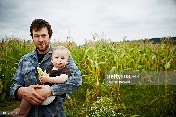 Farmer holding baby boy in front of corn field