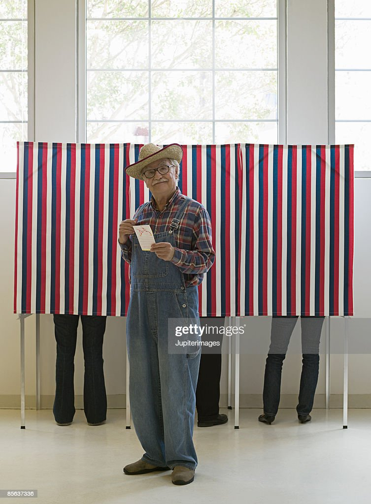 Farmer holding ballot at voting booths : Stock Photo