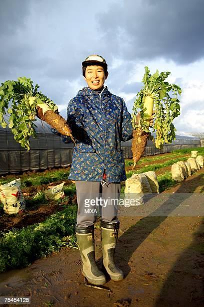 farmer holding daikon radish - 年配の女性一人 ストックフォトと画像