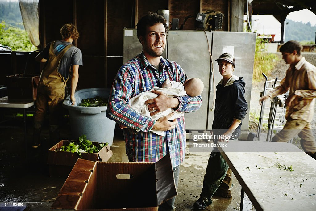 Farmer holding infant standing in work shed : Stock Photo