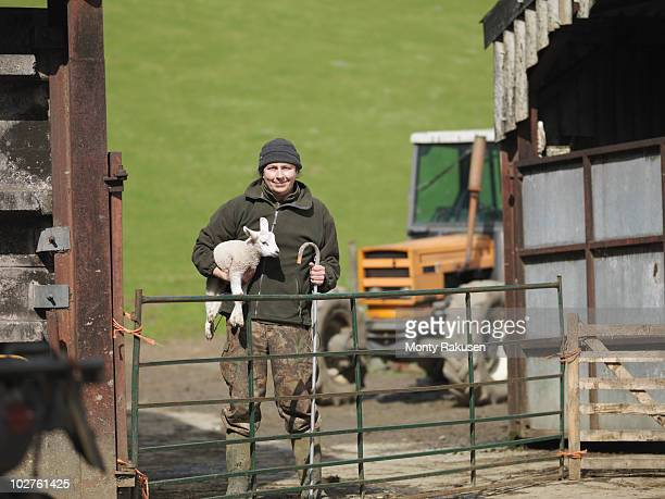 Farmer holding lamb and stick
