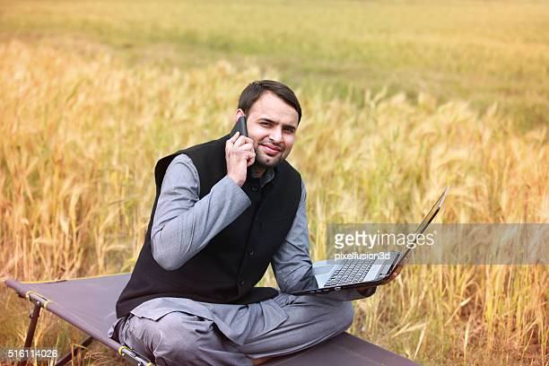 Farmer holding laptop and talking on smartphone