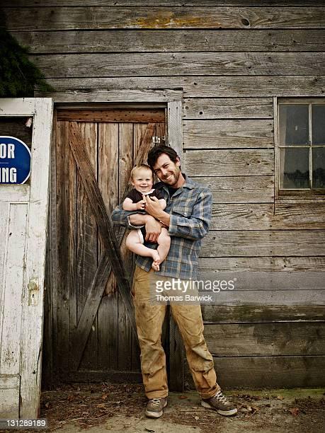 Farmer holding smiling baby boy