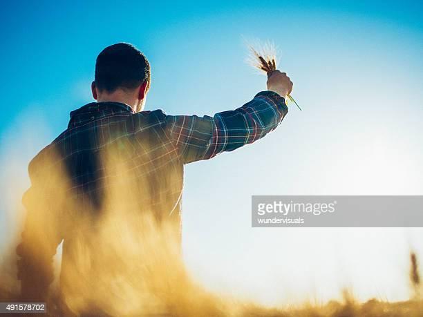 Agriculteur tenant vous dans un champ de blé avec un ciel bleu