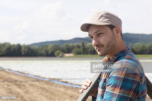 farmer in field carrying pipe on shoulder - sigrid gombert fotografías e imágenes de stock