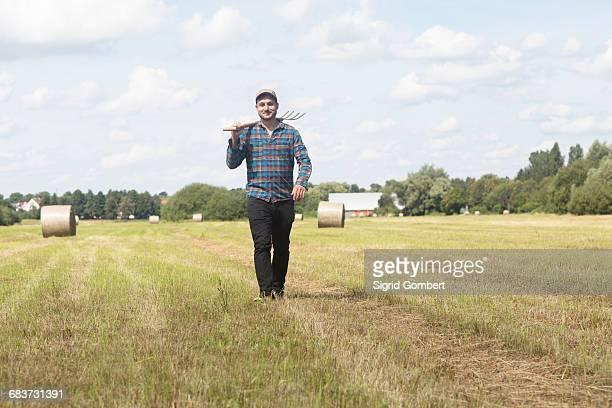 farmer in field carrying spade on shoulder - sigrid gombert stock-fotos und bilder