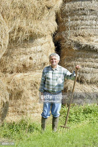 farmer in front of stacked bales of hay