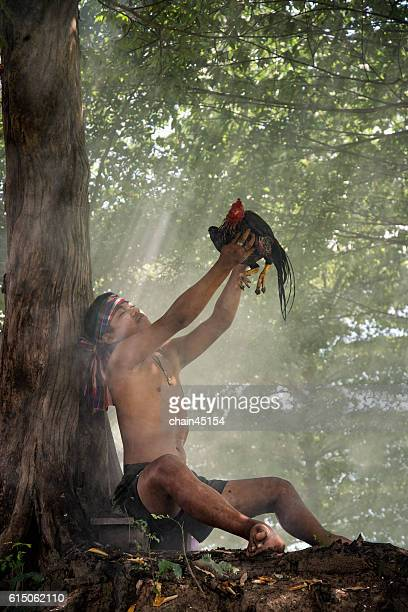 Farmer in the field holding a chicken, healthy lifestyle and organic farming concept in Thailand culture country at Chiangmai, Thailand.