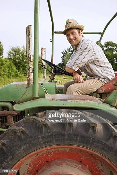 Farmer in tractor ploughing field, smiling, portrait